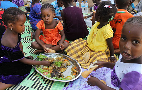 Children in Gambia eating food provided by Penny Appeal